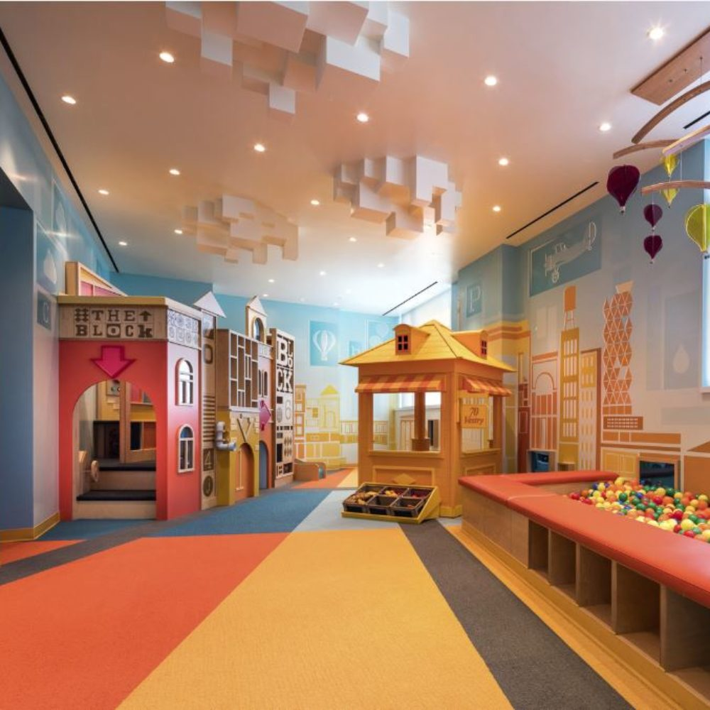 Interior view of 70 Vestry residence kids room in New York City. Has colorful floors, tables for play and shelves.