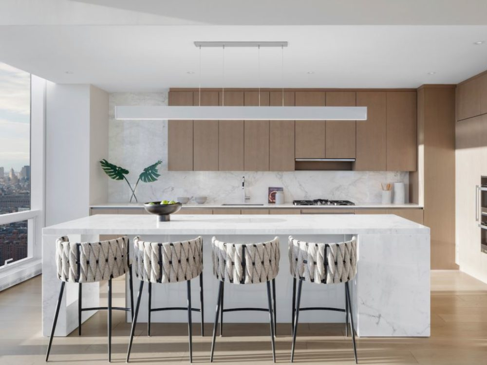 Interior view of 15 Hudson Yards residential kitchen in New York City. Has wood floors, white walls, a counter and chairs.
