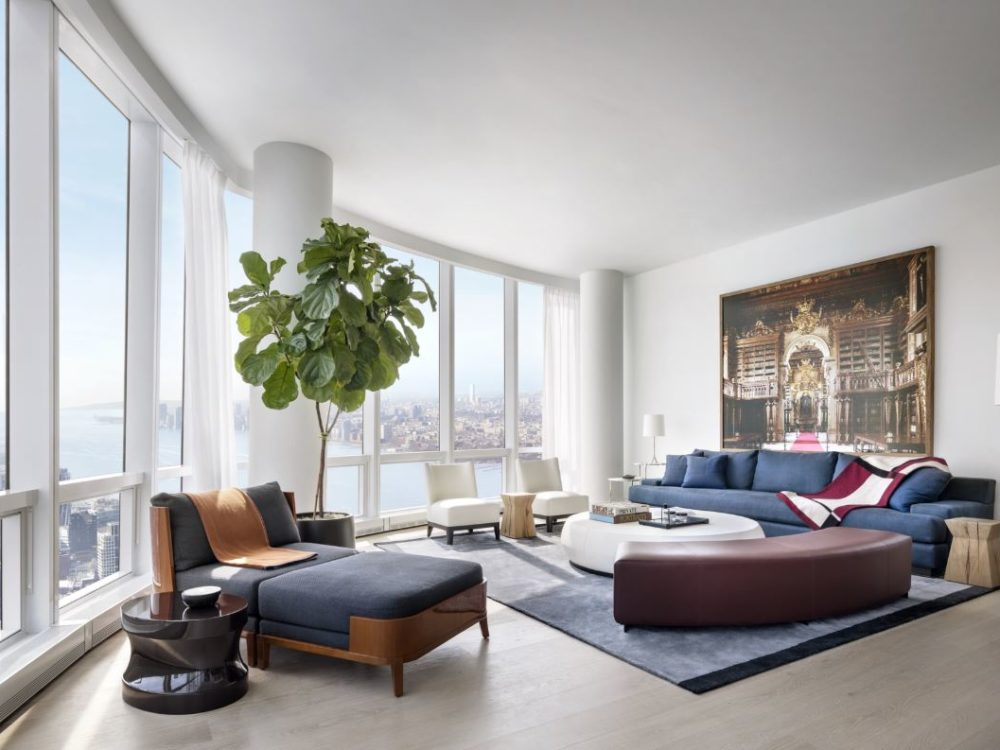 View of residential corner living room in 15 Hudson Yards with a wide view of New York City. Includes couches and chairs.
