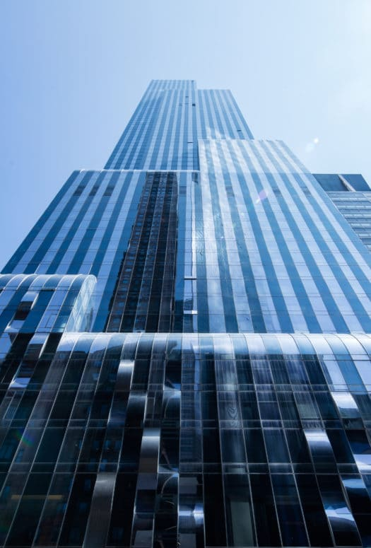 Street view of One 57 luxury condos in New York. Looking up at the residential tower with sun reflecting off the windows.