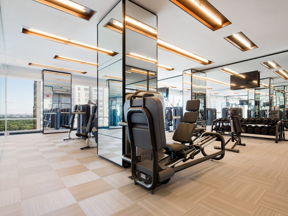Gym at One 57 luxury condos in New York. Mirror walls, free weights, and cardio equipment with large windows for city views.