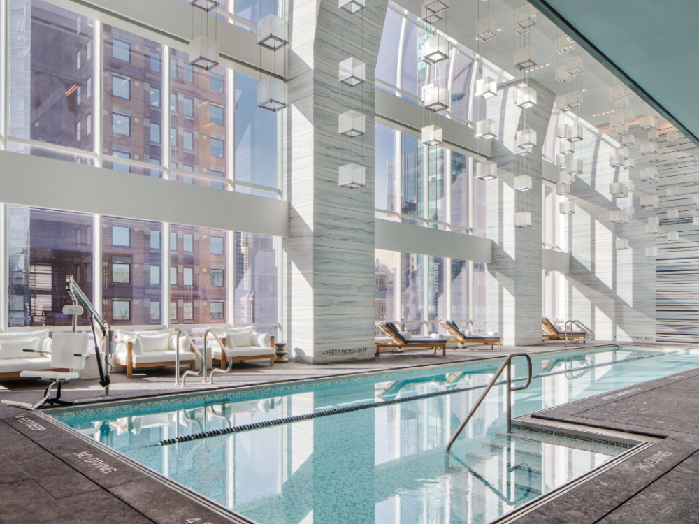 Indoor pool with seating along the floor-to-ceiling windows at One 57 luxury condominiums in New York City.