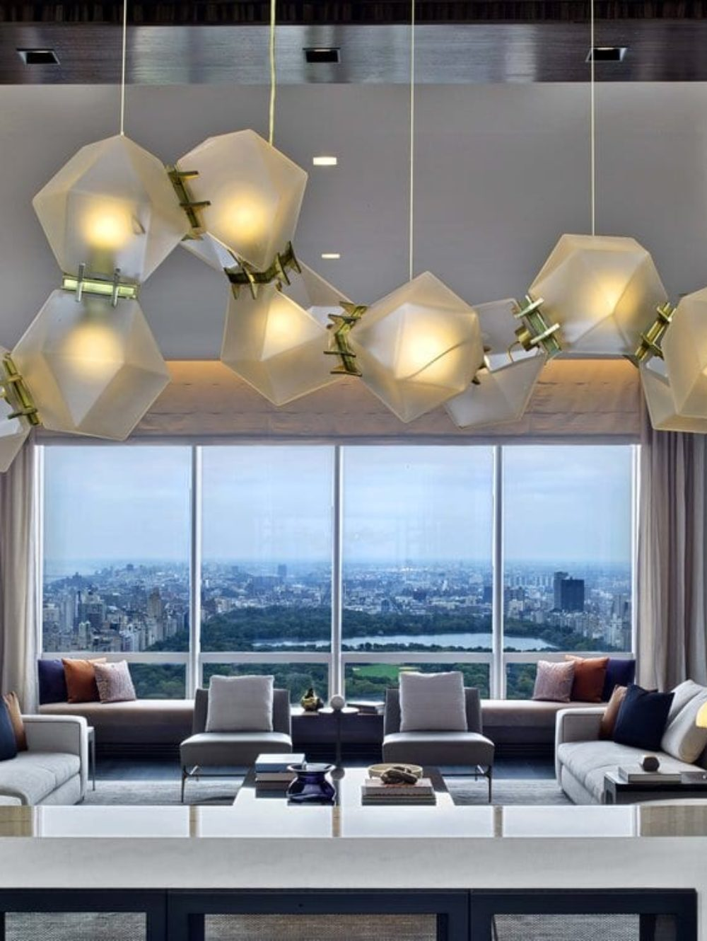 Living room with city views at One 57 condos in New York City. Hanging lights and bookshelves frame living room entrance.