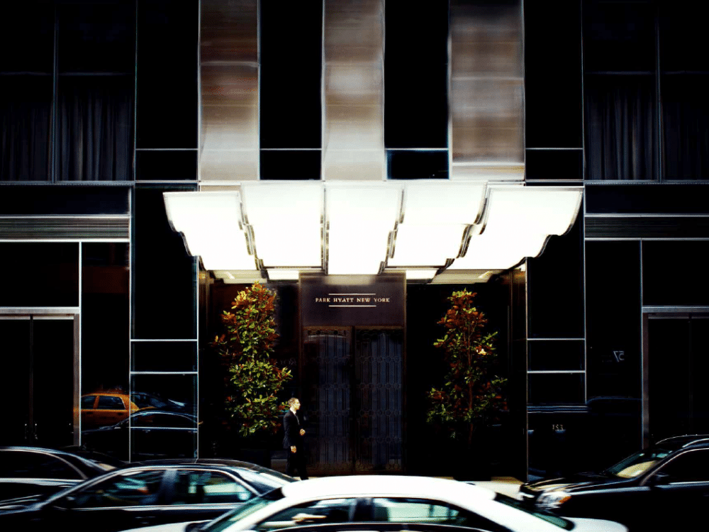 Street view of entrance to One 57 condos in New York. Night-time picture showing front doors with potted trees and canopy.