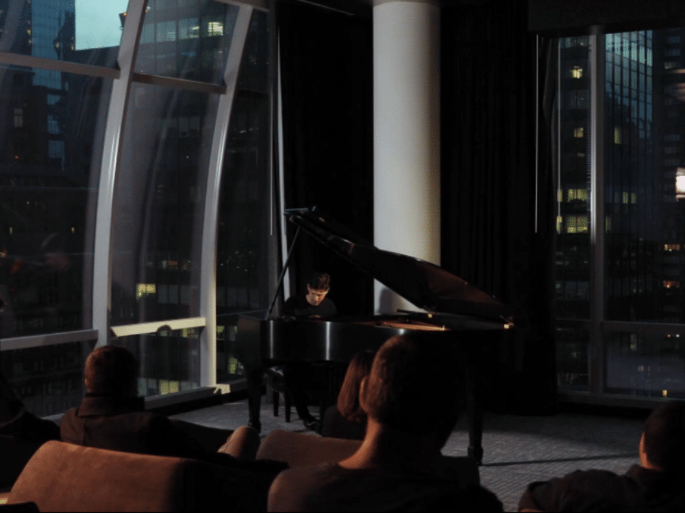 Screening room at One 57 condos in NYC. Man playing the piano with a small audience with dimmed lights and large windows.