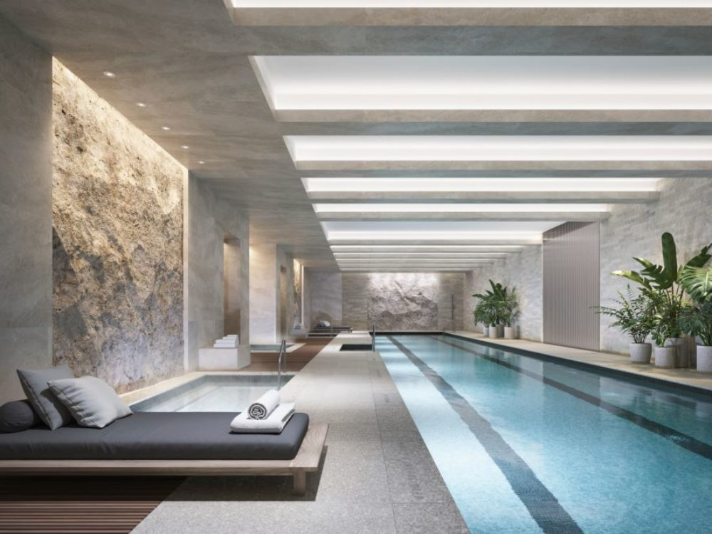 Interior view of 70 Vestry residence indoor pool in New York City. Has lounge beds, light walls and decorative plants.