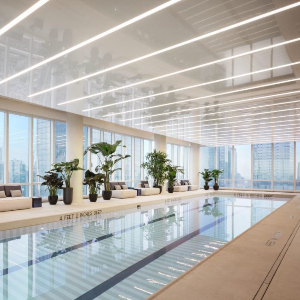 View of lap pool inside 15 Hudson Yards condominiums in New York City. Includes sitting areas and plants with glass windows.