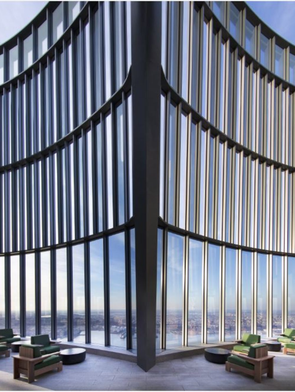 View of rooftop lounge on top of 15 Hudson Yards condominiums with view of New York City. Includes detailed glass structure.