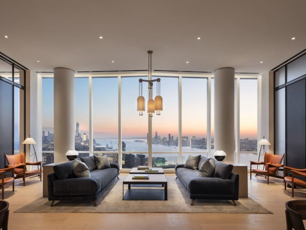 View of conference room, with furniture, inside 15 Hudson Yards condominiums with a window view of New York City at sunset.
