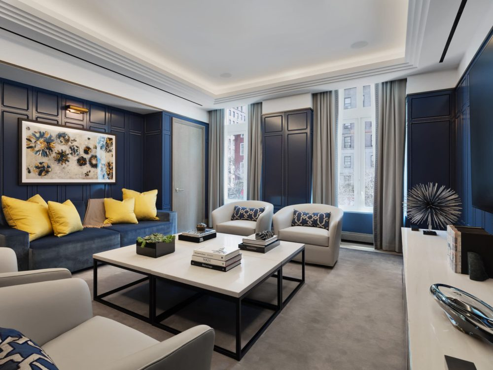 1010 Park Avenue screening room overlooks NYC and includes blue and white mohair velvet sofas and custom timber wall panels.