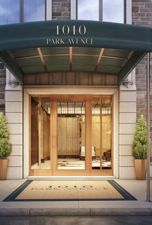 1010 Park Avenue Building Entry New York City. Front Doors of Brick Building with Canopy and Potted Trees Framing the Door.