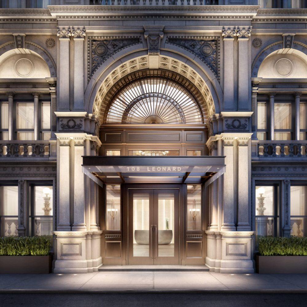 Modern renaissance grand entrance to 108 Leonard condominiums New York City at night with lights illuminating the door.