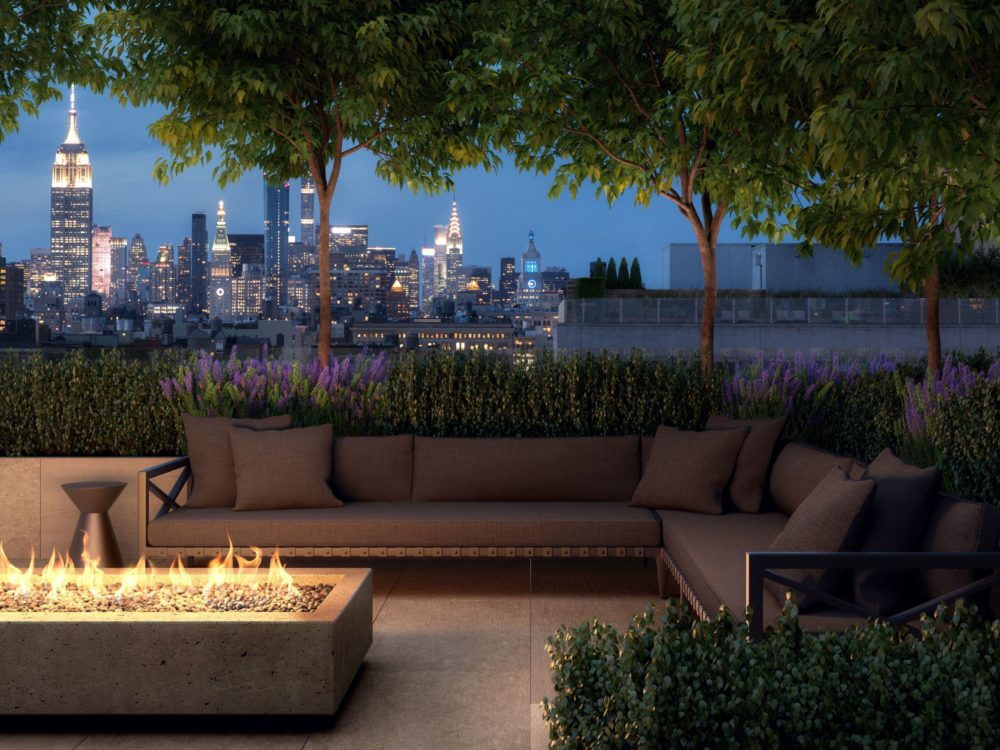108 Leonard exclusive rooftop garden featuring cabana lounges, an electric fireplace and view of New York City at night.