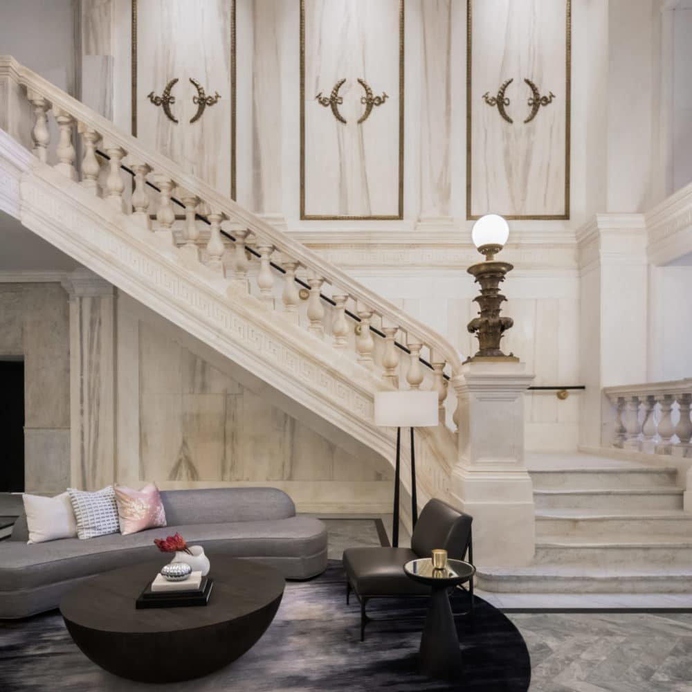 Interior view of a white, modern renaissance staircase and dark furniture part of the entrance of 108 Leonard in NYC.