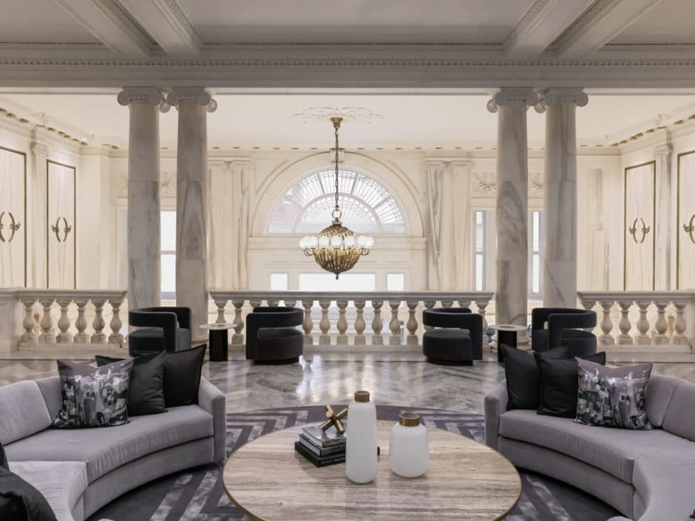 Interior modern sitting area inside 108 Leonard in NYC. It is decorated with marble columns and white and black furniture.