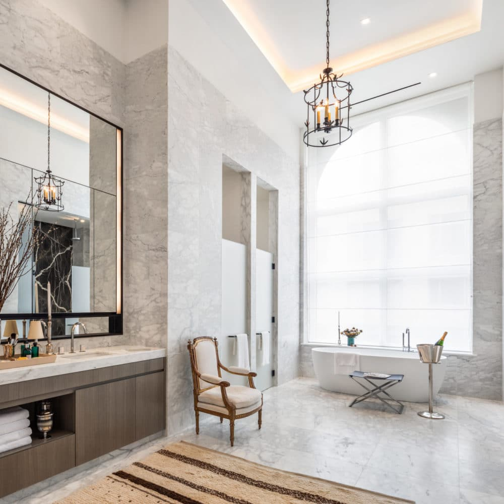 Interior view of a bathroom in 108 Leonard with white marble walls, a wide mirror, and a window overlooking New York City.