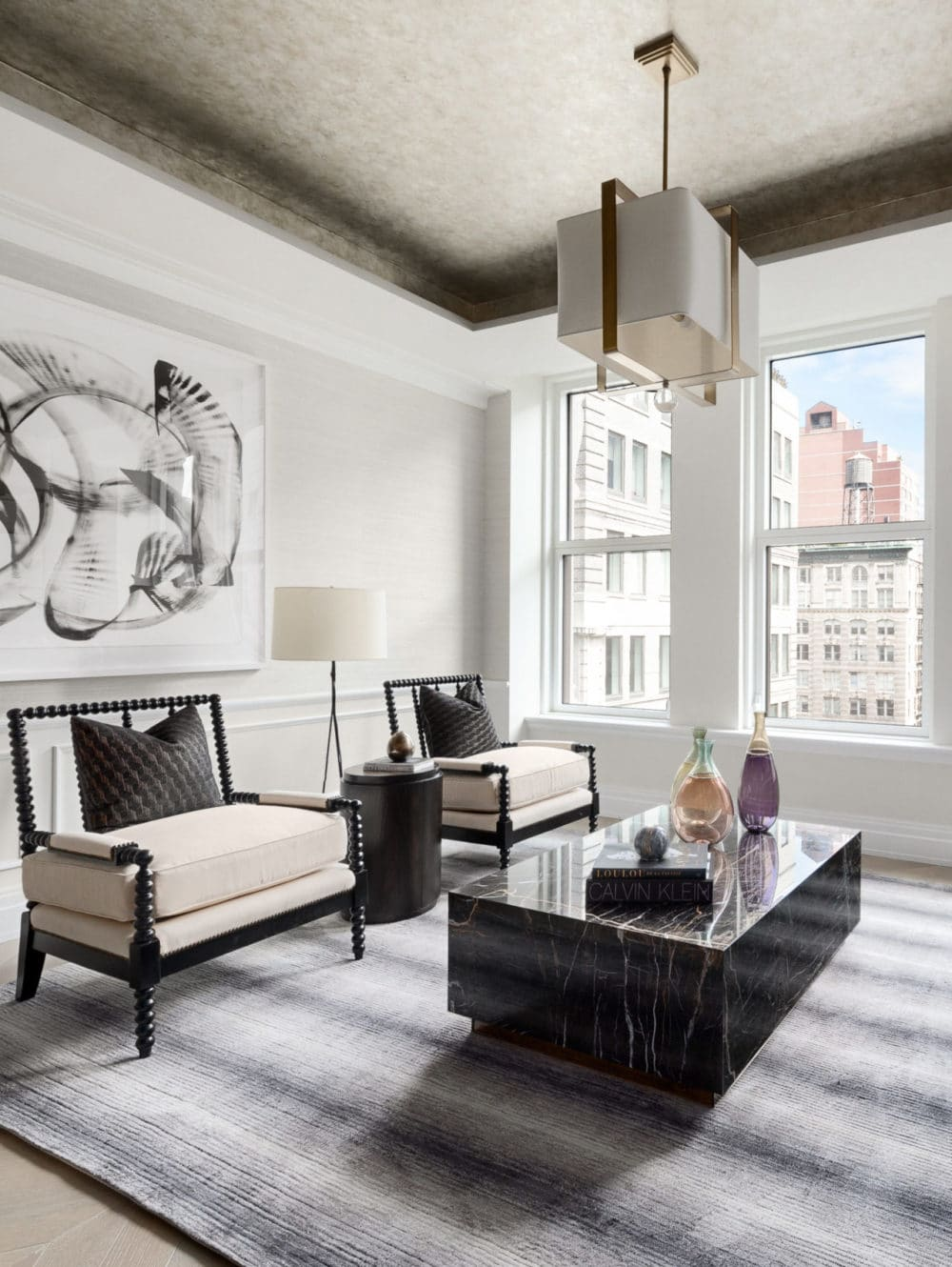 Interior view of a living room with classic white walls and black furniture in 108 Leonard condominiums in New York City.