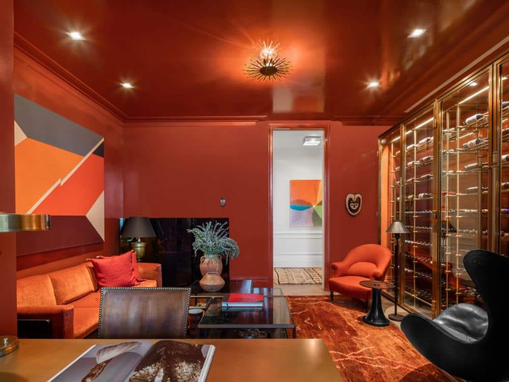 Interior view of a living room with bright red walls and colorful furniture in 108 Leonard condominiums in New York City.