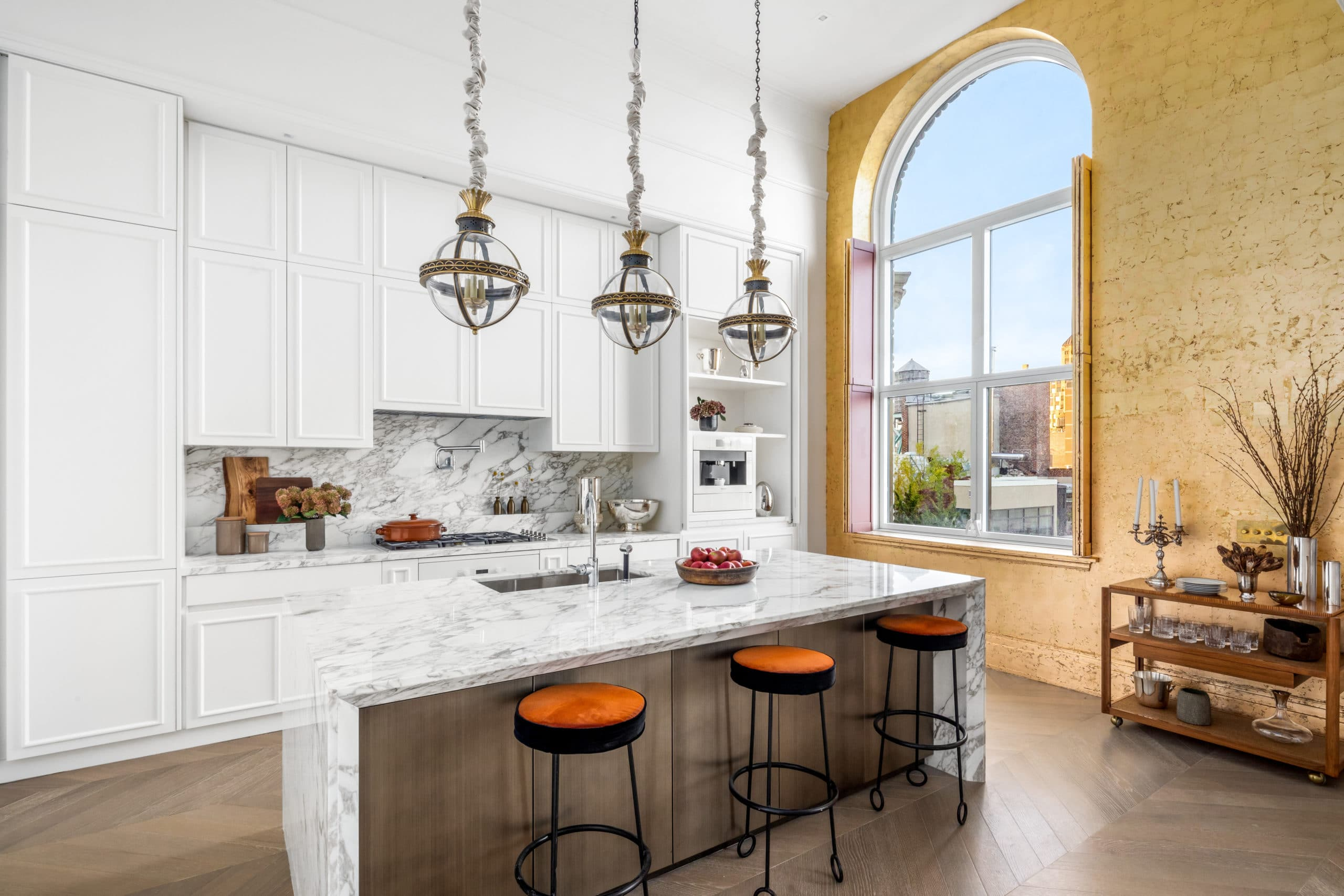 Interior of a kitchen in 108 Leonard with white walls accented with a yellow wall and a window overlooking New York City.