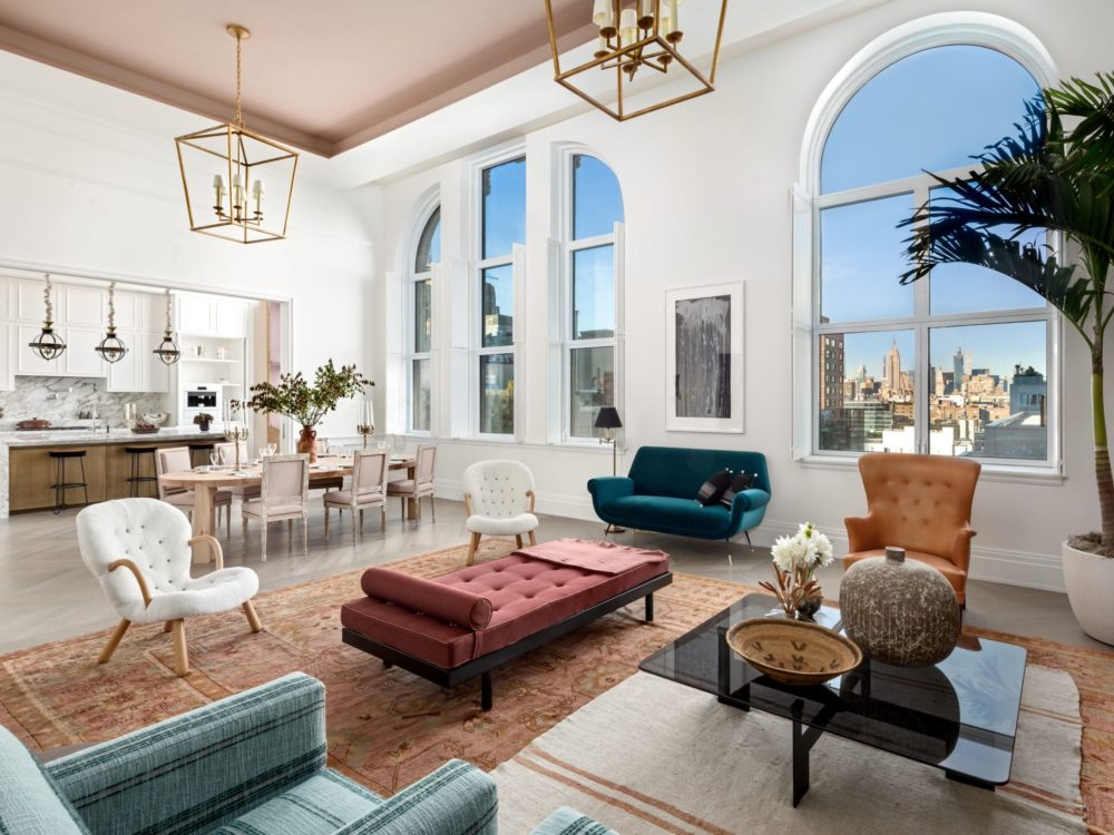Interior view of a spacious living room and kitchen area inside 108 Leonard with windows that look out at New York City.