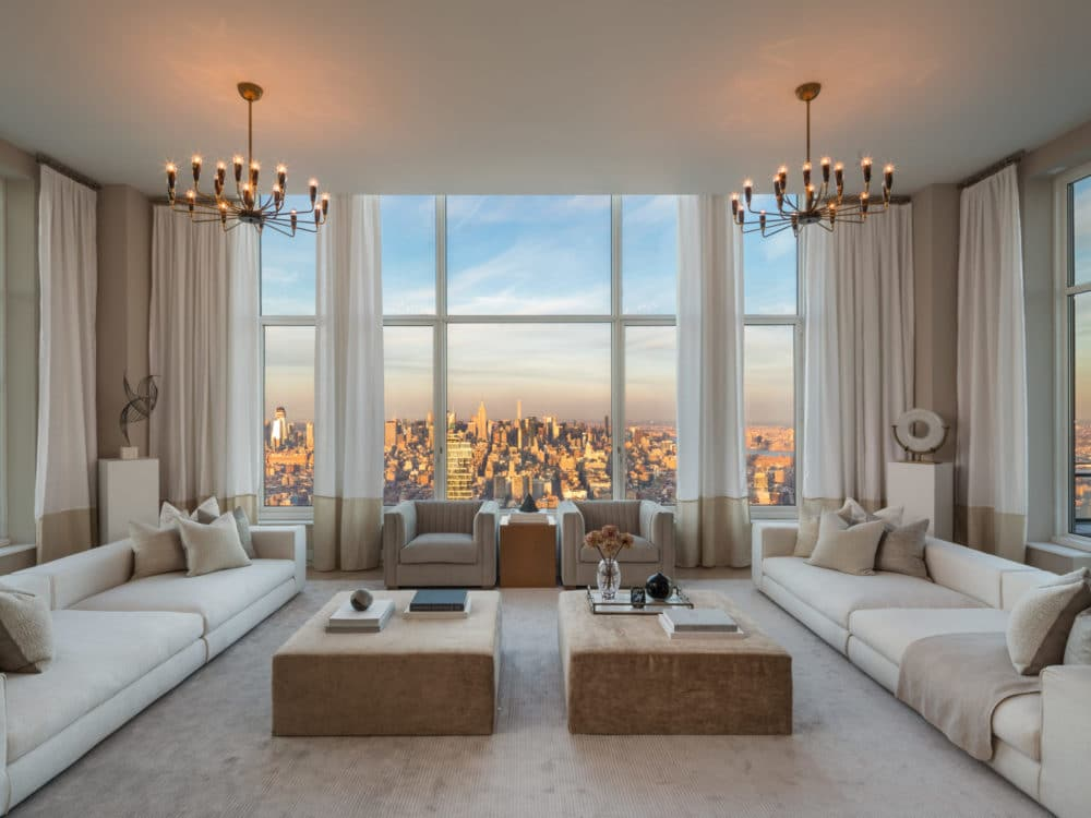 Interior view of living room inside 30 Park Place condominiums with window view of NYC. Has white walls and wood tables.
