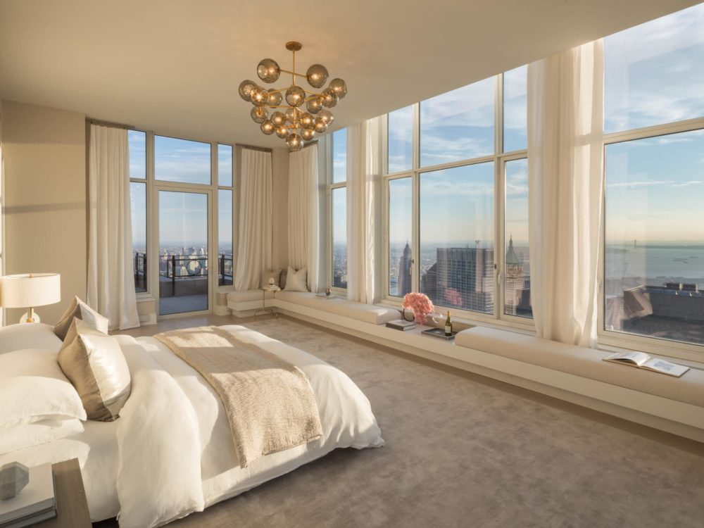 Interior view of 30 Park Place residence master bedroom with white bed facing window view of New York City during the day.