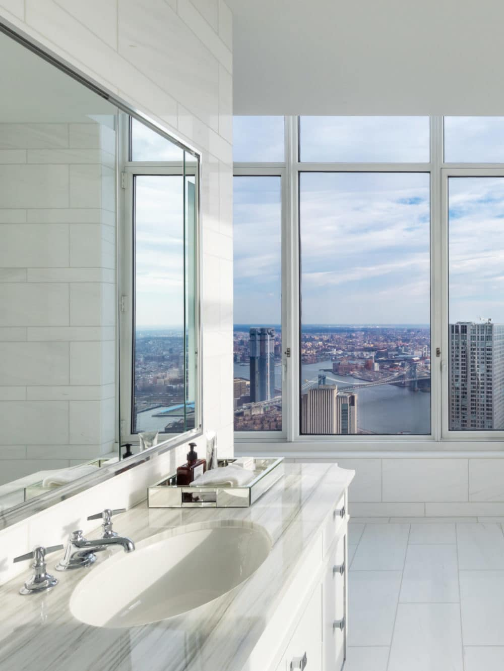 Interior view of white bathroom in 30 Park Place with window view of New York City. Includes bathtub and sink area.
