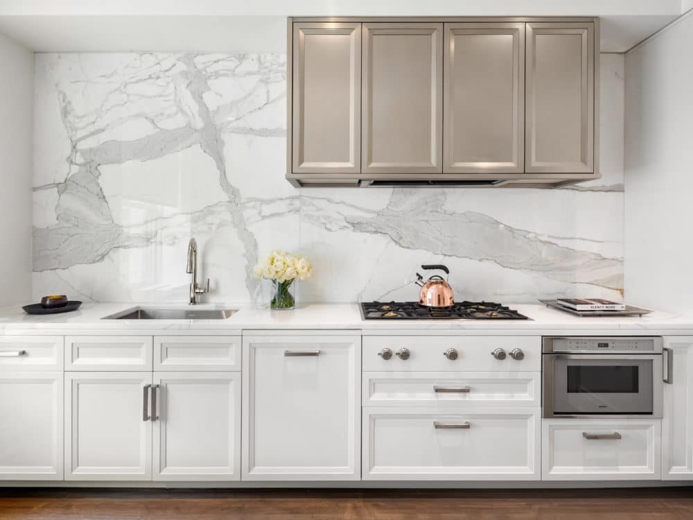 Kitchen counter with white cabinets, a gold range hood and marble backsplash in The Belnord Apartments in New York City.