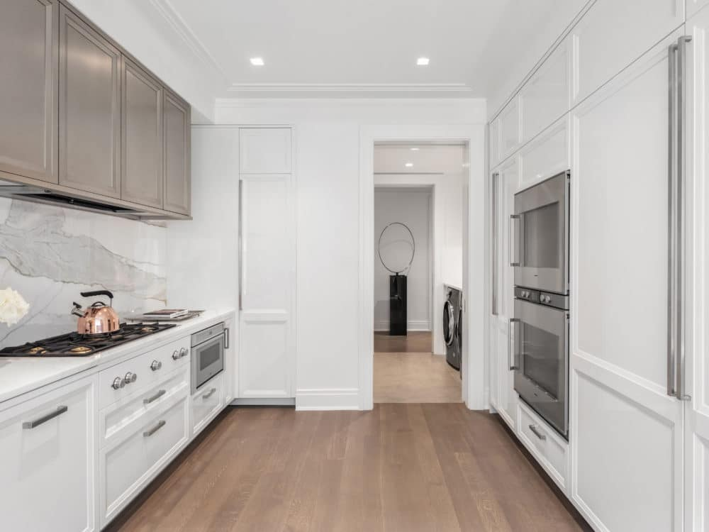 Interior view at The Belnord luxury apartments in New York. Looking through the kitchen into the laundry room and hallway.