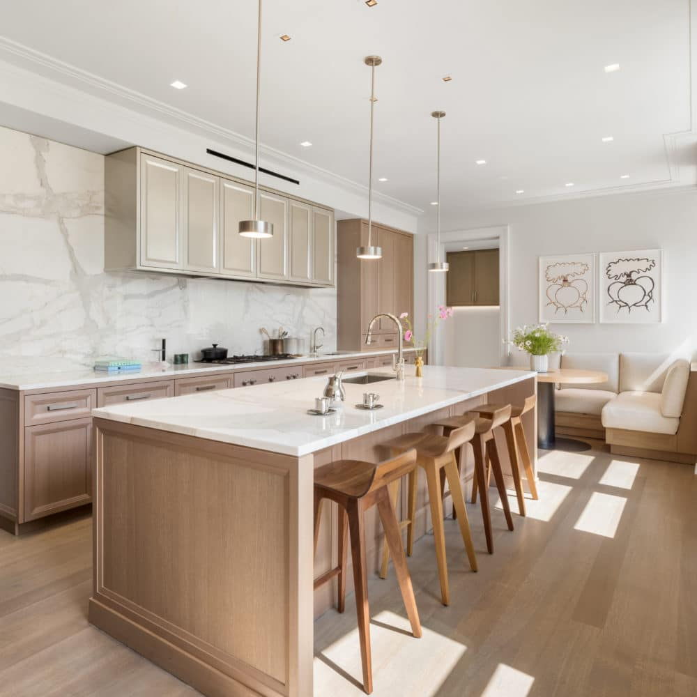 Open kitchen with breakfast nook in The Belnord apartments, NYC. White walls and countertops with oak floors and finishes.