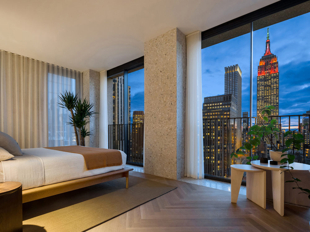 Corner bedroom at The Bryant luxury condominiums in NYC. Tall windows with a view of the city, hanging lights and a bed.
