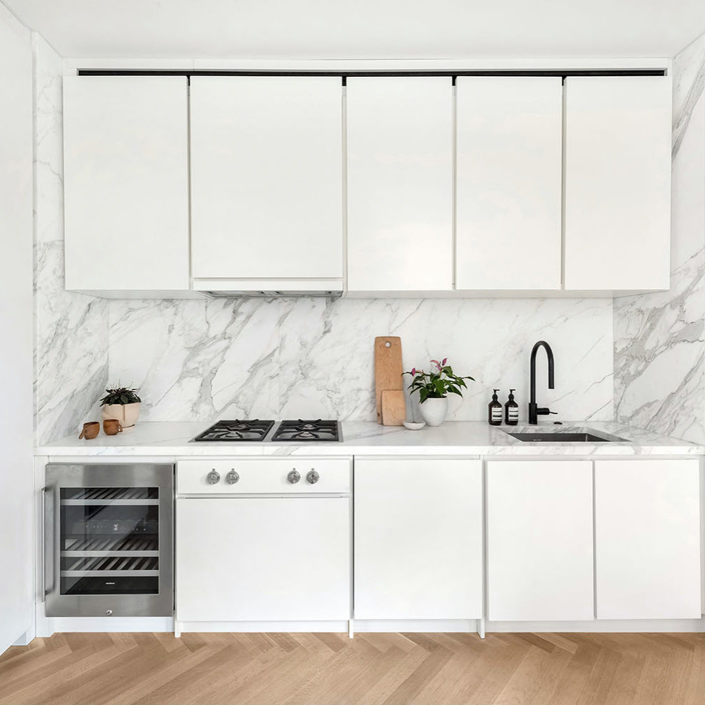 Kitchen at The Bryant condos in NYC. White cabinets and white counter tops with stainless steel appliances and oak floors.