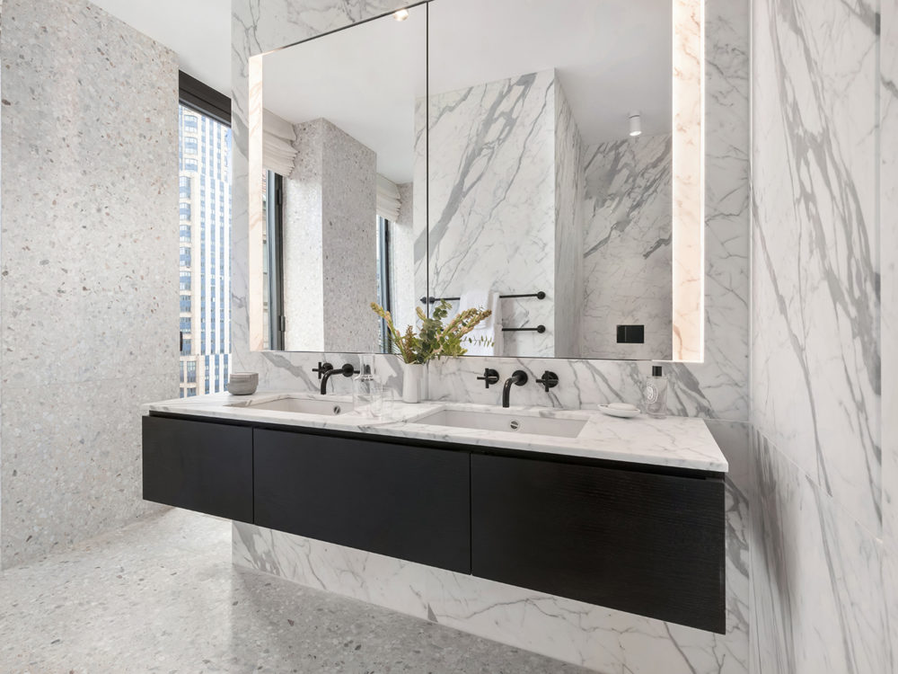 Bathroom in The Bryant condos in New York. Double vanity with white marble top, large mirror and floor-to-ceiling windows.