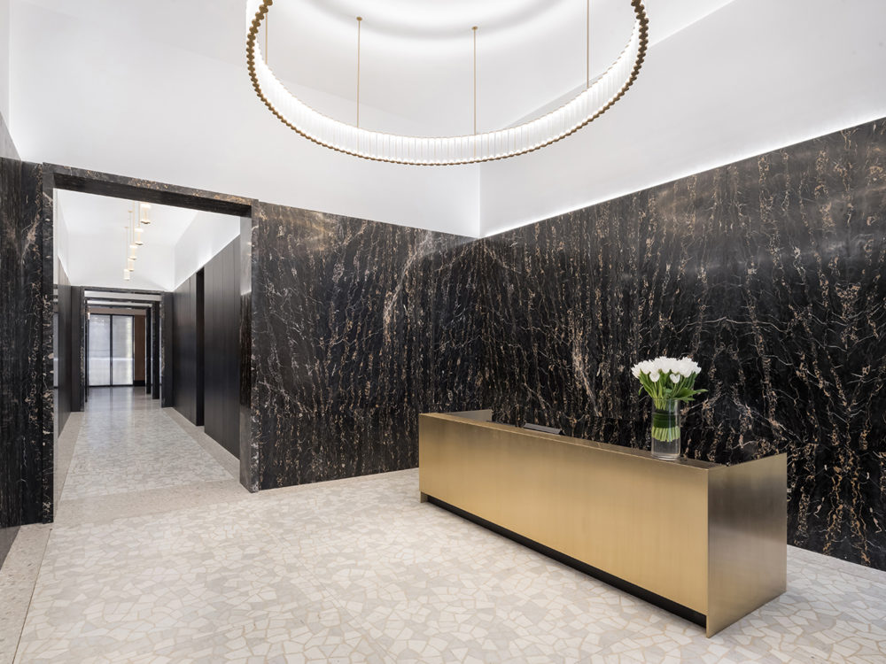 Lobby at The Bryant residences in New York. Light gray floors and a gold desk with hanging chandelier and black marble walls.