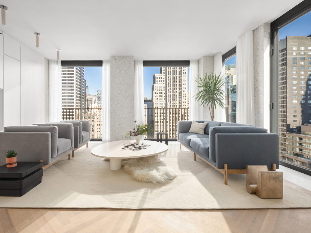 Corner living room with oversized windows, blue furniture and a white table with city views of New York at The Bryant condos.
