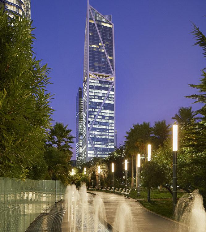 Exterior street view of 181 Fremont condominiums with a night time view of San Francisco. Includes pathway and fountain.