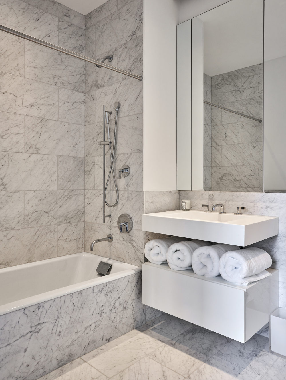 White marble bathroom in the Park Loggia condominiums in New York City. White vanity and tall mirror with shower & tub combo.