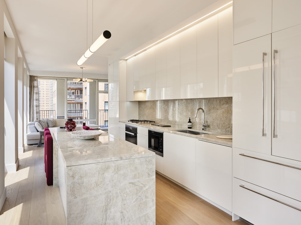 Kitchen in the Park Loggia luxury condos in New York. White cabinets, quartzite countertops & oak floors with natural light.