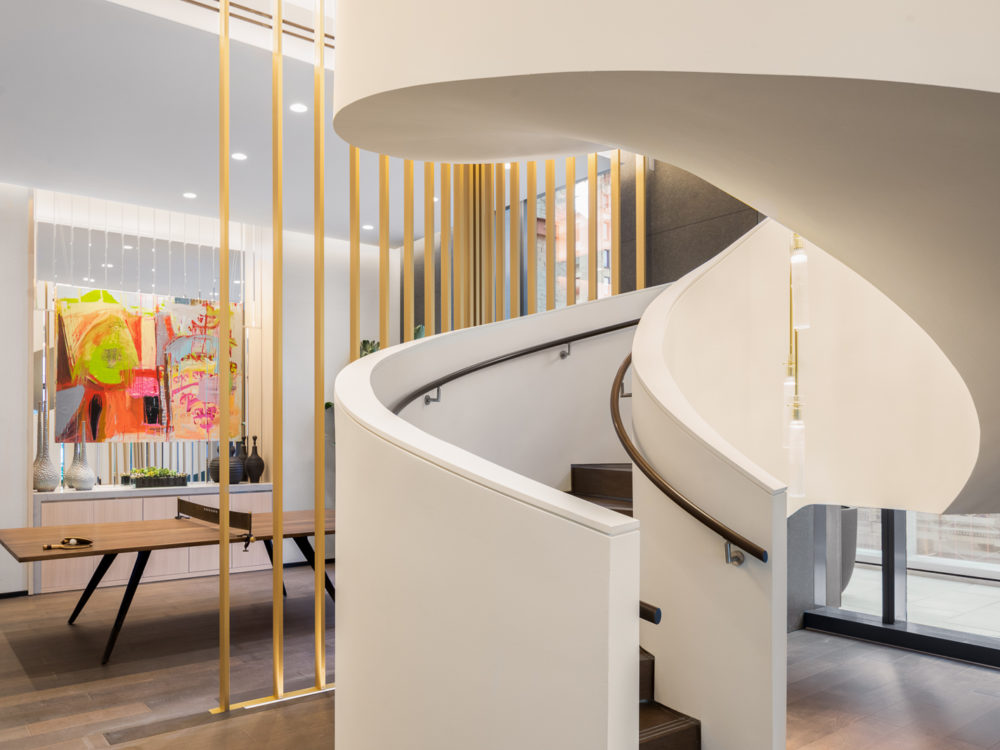 Interior view of 277 Fifth Avenue residence lobby with white spiral staircase and wooden floors located in New York City.