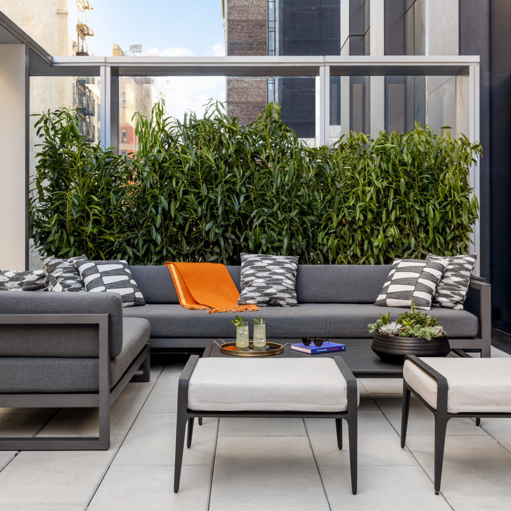 Exterior private terrace located at 277 Fifth Avenue condominiums located in NYC. Has grey couches and white feet rests.