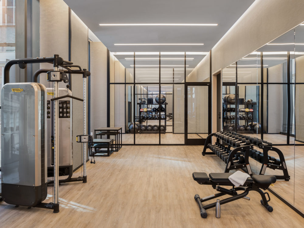 Interior view of 277 Fifth Avenue residence fitness center in NYC. Has weight lifting and cardio equipment with wood floors.