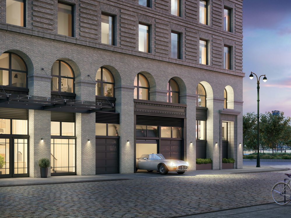 Exterior view of 57 Vestry condominiums entrance in New York City. Has view of street, a car, and the sunset.