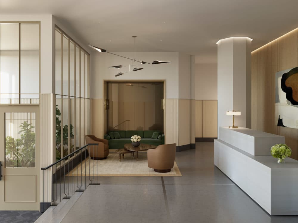 Interior view of 67 Vestry condominiums lobby in New York City. Has tile floors, brown chairs and white desk.