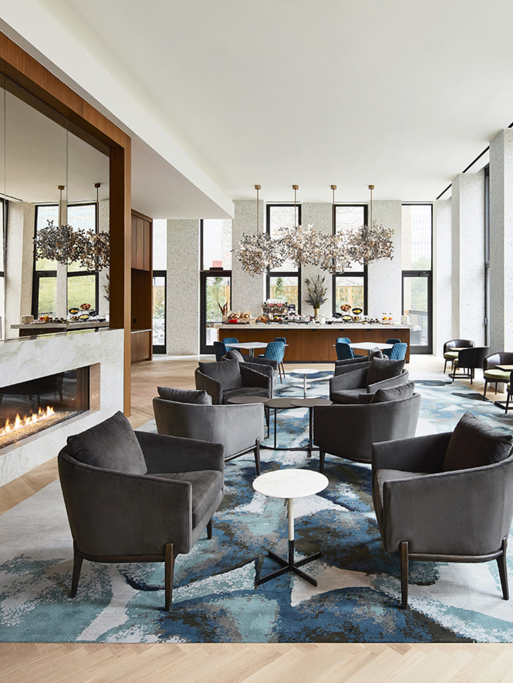 Living room lounge at The Bryant condominiums in New York. Large room with multiple tables, a bar and a built-in fireplace.