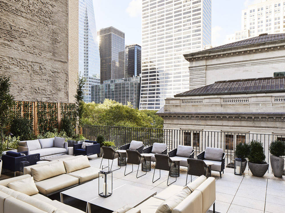 Outdoor terrace with couches, chairs, and potted plants over looking Bryant Park at The Bryant luxury condos in New York.