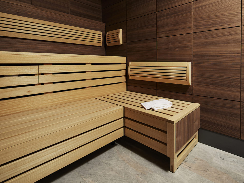 Sauna at The Bryant condominiums in New York City. Wood bench with a towel resting on the corner and wood walls.