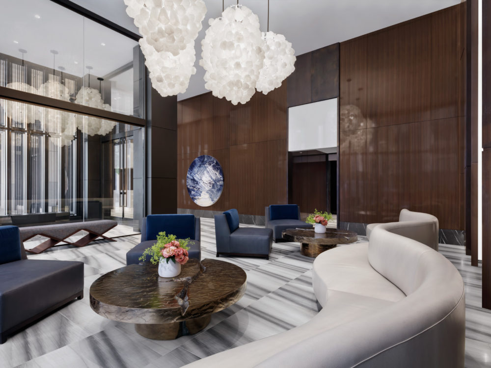 Club room at the Park Loggia luxury condos in NYC. Large room with chandeliers, tall windows, and several seating areas.