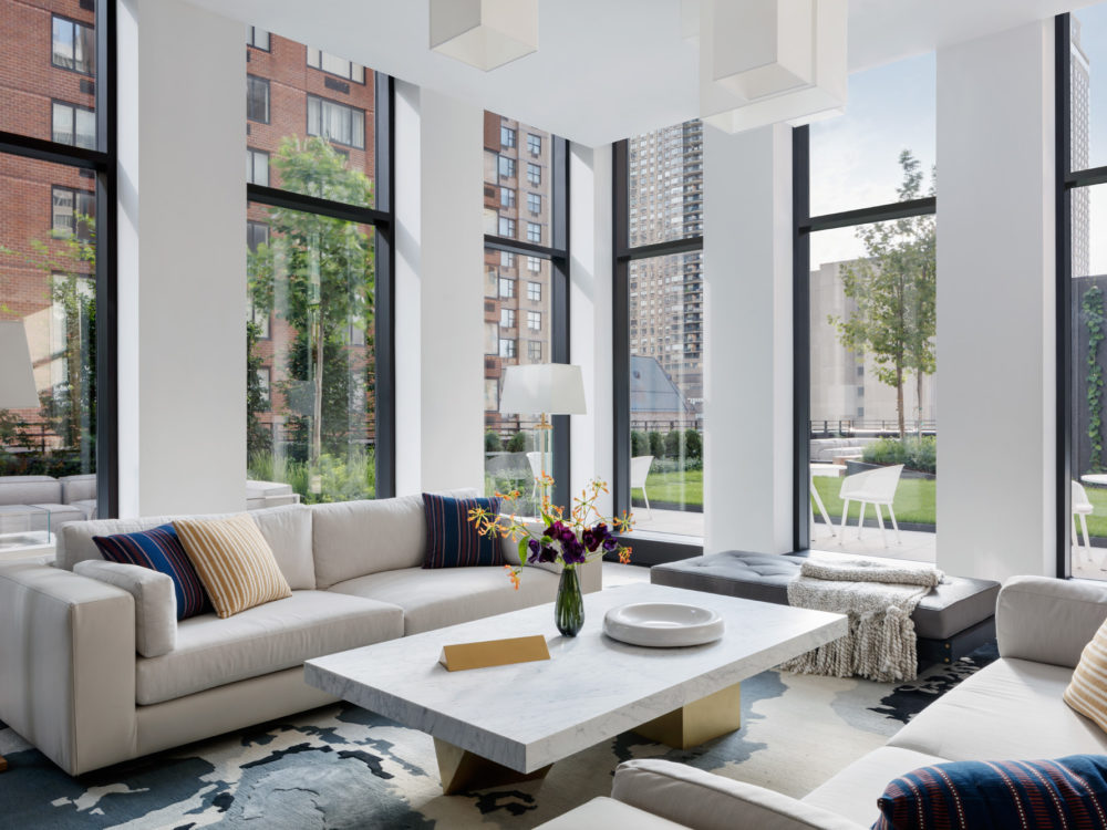 Community room at the Park Loggia condos in New York. Large room with tall windows, couches, and table with natural light.