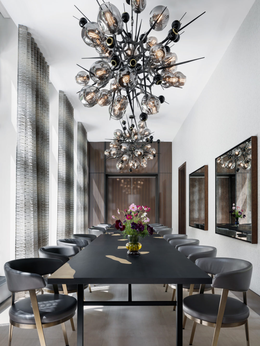 Private dining room at the Park Loggia luxury condos in New York. Long black dining table, tall windows, & large chandelier.