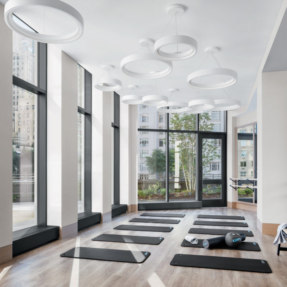 Large fitness studio at the Park Loggia in New York. Tall ceilings with natural light, yoga mats, & barres lining the walls.